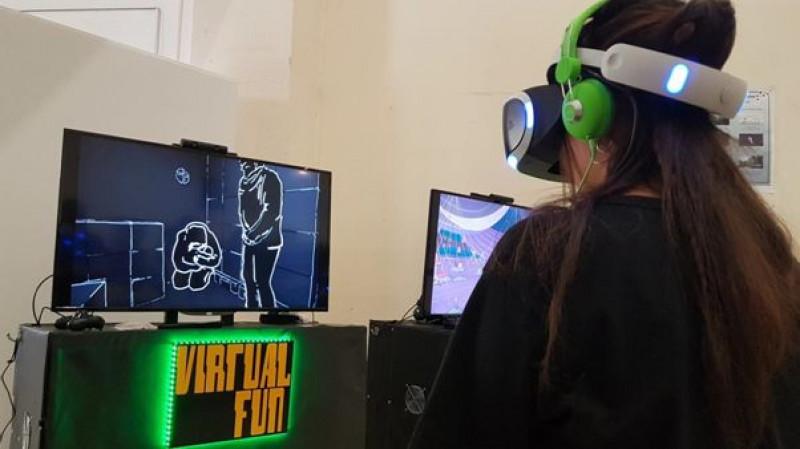 """Besucherin schaut """"Paris Terror"""" auf VR-Brille. Der Film wird zusätzlich auf Bildschirm gezeigt © Ricarda Saleh"""